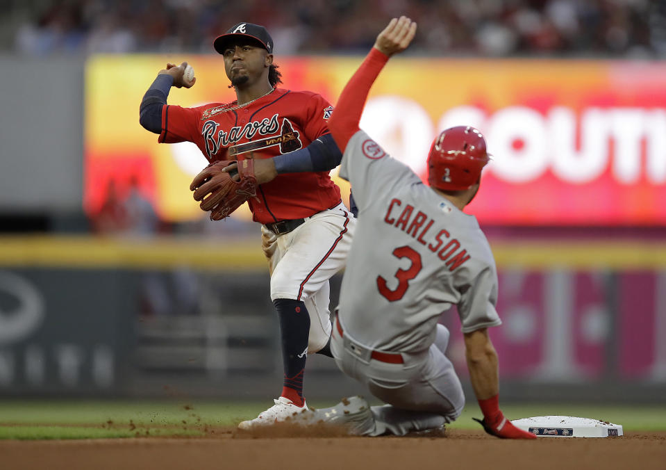 Atlanta Braves' Ozzie Albies, left, prepares his throw to first base to complete a double play after making the out on St. Louis Cardinals' Dylan Carlson (3) during the fourth inning of a baseball game Friday, June 18, 2021, in Atlanta. Cardinals' Nolan Arenado was out at first base. (AP Photo/Ben Margot)