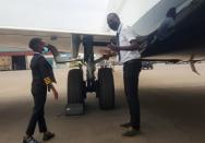 "Ugandan ""Captain"" Graham Shema, listens to his flight instructor, Simon Wadagu Bruno, about functions of some parts of a Bombardier CRJ900 aircraft at the Entebbe International Airport, in Entebbe"