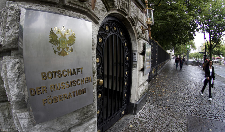 People walk past an entrance of the Russian embassy in Berlin, Germany, Friday, Sept. 4, 2020. Russian President Vladimir Putin's spokesman has brushed off allegations of involvement in the poisoning of his most determined critic, accusing Germany of not providing Moscow with any evidence. (AP Photo/Michael Sohn)