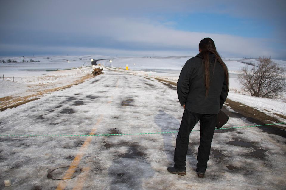 Activist Pete Sands of the Navajo Nation looks out over an area set as a borderline where the police guard a bridge near Oceti Sakowin Camp on the edge of the Standing Rock Sioux Reservation on Dec. 3, 2016, outside Cannon Ball, North Dakota. (Photo: Jim Watson/AFP/Getty Images)