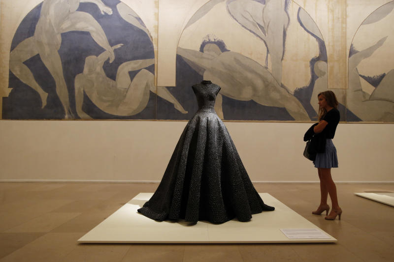 """FILE - In this Sept. 25, 2013 file photo, a visitor, Una Duval age 21, looks at """"Long Dress"""" of woven raffia, silver thread and bead embroidery of Spring Summer 1997 collections by French Tunisian born Fashion designer Azzedine Alaia, presented for the first Paris retrospective of couturier front of """"Lutte des Nymphes"""", 1931 by Matisse at the Museum of Modern Art in Paris. Alaia, a fashion iconoclast whose clingy styles helped define the 1980s and who dressed famous women from Hollywood to the White House, has died at age 77. The French Haute Couture Federation announced Alaia's death on Saturday, Nov. 18, 2017 without providing details. (AP Photo/Francois Mori)"""