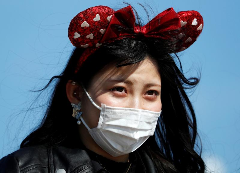 A visitor wearing protective face mask and Minnie Mouse costume, following an outbreak of the coronavirus, is seen outside Tokyo Disneyland in Urayasu, east of Tokyo, Japan February 28, 2020. REUTERS/Issei Kato