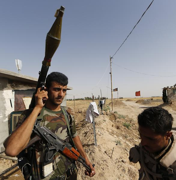 Iraqi Turkmen forces man a checkpoint in the northern city of Taza Khormato, 20 kms south of Kirkuk, on June 21, 2014 (AFP Photo/Karim Sahib)
