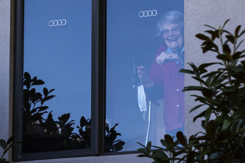 A resident at the Arcare Aged Care facility in Maidstone reacts to media from her window, in Melbourne.