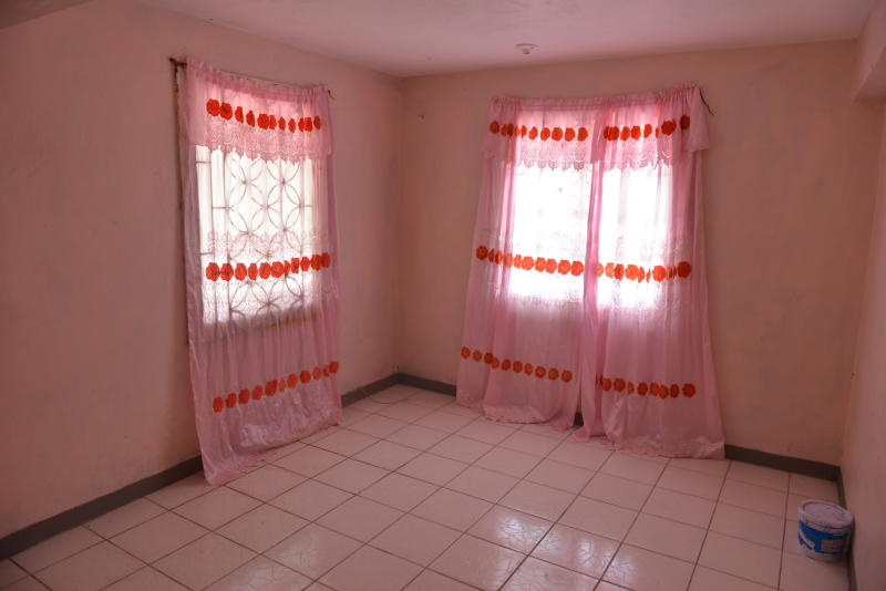 "In this Aug. 3, 2013 photo, pink curtains adorn an empty room that once belonged to Dwayne Jones on the northern outskirts of Montego Bay, Jamaica. Dwayne was a 16-year-old Jamaican who was savagely murdered by a mob last month after they found out he was attending a street dance party in women's clothing, a wig and heavy makeup. For years, Jamaica's gay community has lived so far underground that their parties and church services were held in secret locations. Most gays have stuck to a ""don't ask, don't tell"" policy of keeping their sexual orientation hidden to avoid scrutiny or protect loved ones. (AP Photo/David McFadden)"