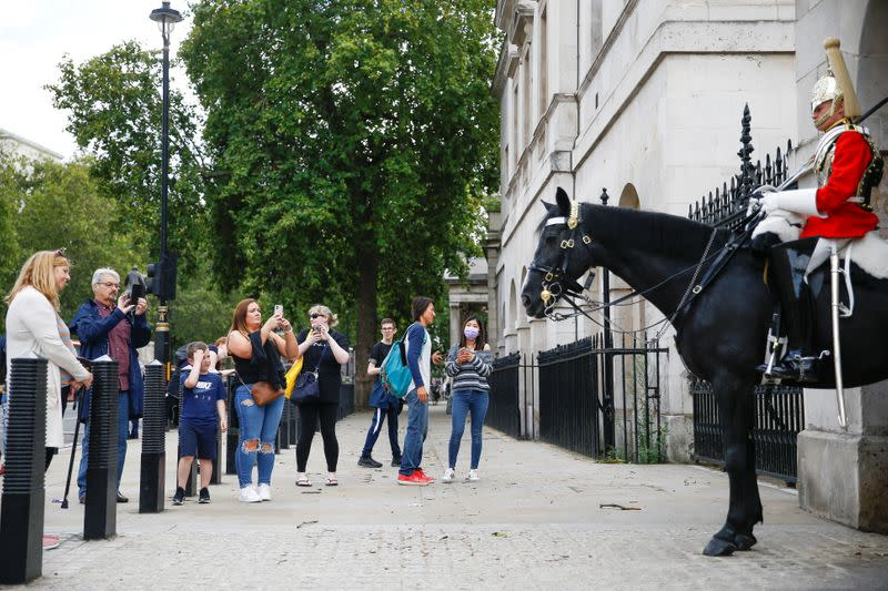 FILE PHOTO: People stop to look at the Household Cavalry at Horse Guards Arch, amid the coronavirus disease (COVID-19) outbreak, in London