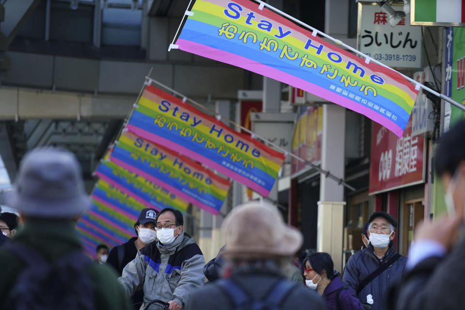 """People wearing protective masks to help curb the spread of the coronavirus wait for a traffic light near banners reading """" Stay Home"""" hoisted along a shopping street in Tokyo Thursday, Jan. 14, 2021. The Japanese capital confirmed more than 1500 new coronavirus cases on Thursday. (AP Photo/Eugene Hoshiko)"""