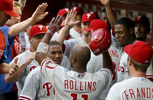Philadelphia Phillies' Jimmy Rollins, foreground, gets high-fives from teammates in the dugout after his home run against the Arizona Diamondbacks during the first inning of a baseball game on Friday, May 10, 2013, in Phoenix. (AP Photo/Ross D. Franklin)