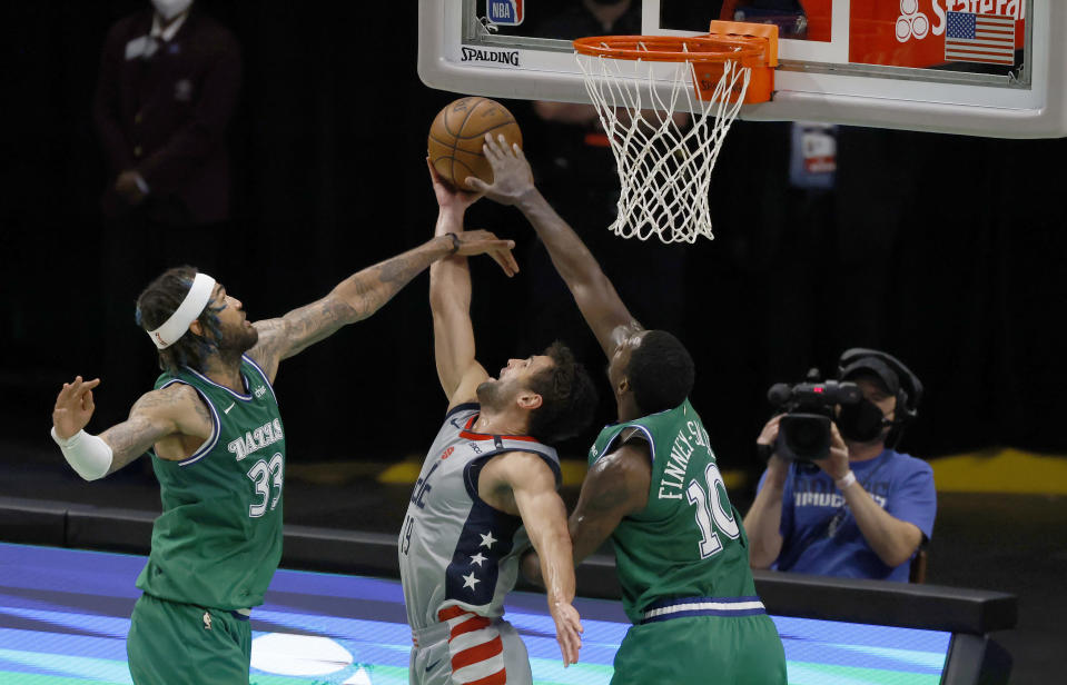 Washington Wizards guard Raul Neto (19) goes up to shoot as Dallas Mavericks forward Dorian Finney-Smith (10) center Willie Cauley-Stein (33) defend the basket during the first half of an NBA basketball game Saturday, May 1, 2021, in Dallas. (AP Photo/Ron Jenkins)