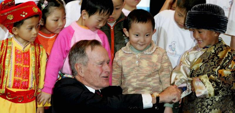 Former President George H.W. Bush shakes hands with young children in China that have received cleft lip surgery through Simle Train on November 15, 2005.