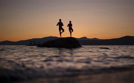 A couple stand on a rock facing the sunset along the shores of English Bay in Vancouver