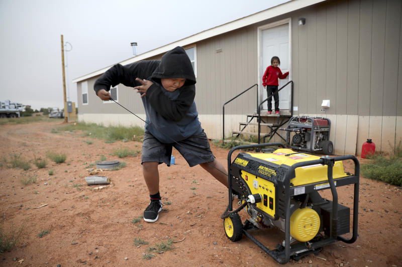 In this Wednesday, May 8, 2019 photo, Jayden Long, 13, starts the generator behind his Kaibeto home on the Navajo Reservation in Arizona, so that he can charge his cell phone inside the family home. An ambitious project to connect homes to the electric grid on the country's largest American Indian reservation is wrapping up. Utility crews from across the U.S. have volunteered their time over the past few weeks to hook up about 300 homes on the Navajo Nation. (AP Photo/Jake Bacon)