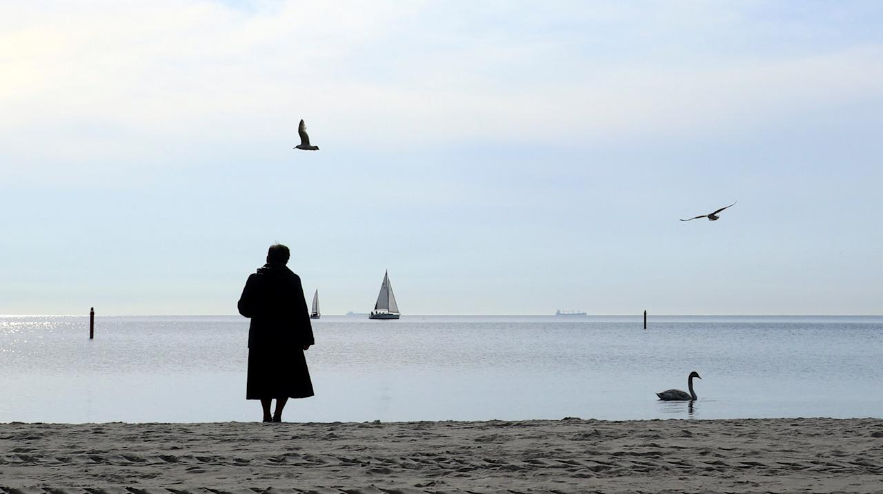A woman, wrapped up against the cold wind, stands on the beach as she watches a swan and yachts in Gdynia, Poland, April 27, 2017.  REUTERS/Russell Boyce       TPX IMAGES OF THE DAY