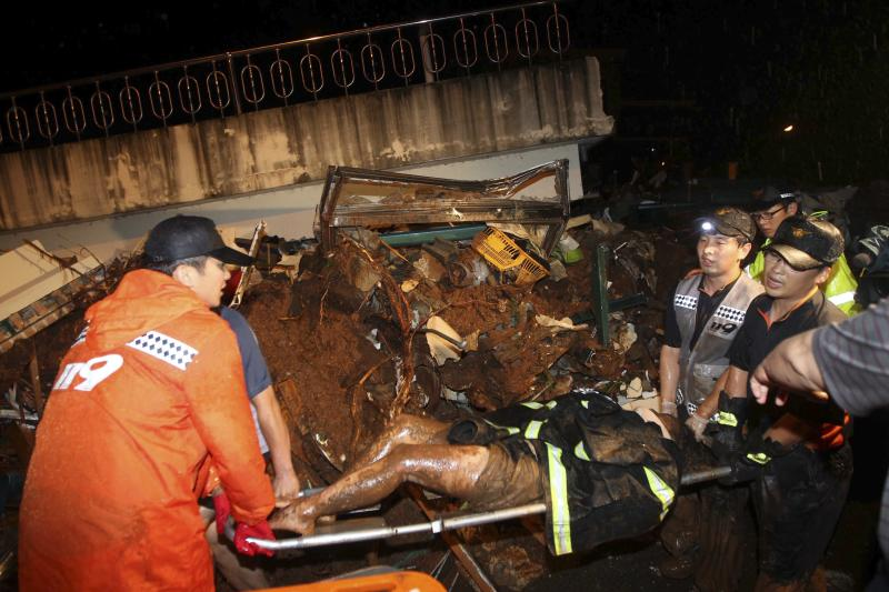 South Korean rescue workers carry a survivor who was rescued from a collapsed house as a midnight landslide caused by torrential rains swept away several houses in Chuncheon, South Korea, Wednesday, July 27, 2011. Heavy rain sent the landslide barreling into a resort in a northern South Korean town Wednesday. (AP Photo/Lee Sang-hak)  KOREA OUT