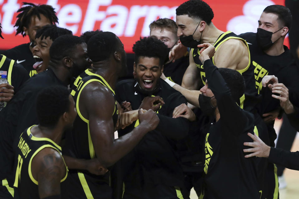 Oregon's Aaron Estrada, center, and teammates celebrate their team's win over Oregon State and their second consecutive Pac-12 regular-season conference title following an NCAA college basketball game in Corvallis, Ore., Sunday, March 7, 2021. (AP Photo/Amanda Loman)