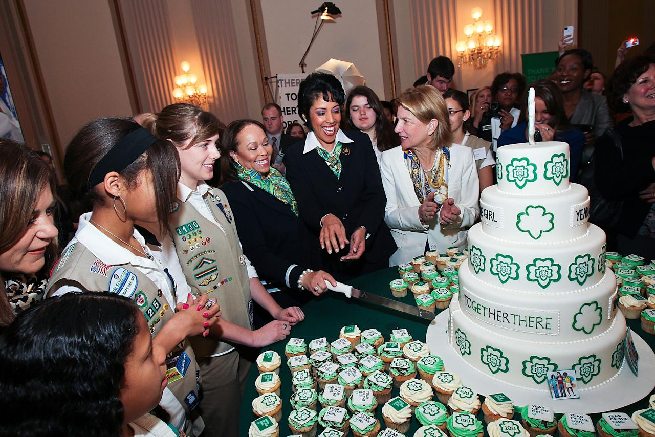WASHINGTON, DC - FEBRUARY 01: Connie L. Lindsey, National President, Girl Scouts of the USA, and Anna Maria Chavez, Chief Executive Officer of Girl Scouts of the USA, cut birthday cake at Girl Scouts At 100: The Launch of ToGetHerThere at Capitol Hill Cannon House Office Bldg, Caucus Room on February 1, 2012 in Washington, DC.  (Photo by Paul Morigi/Getty Images for Girl Scouts of America)