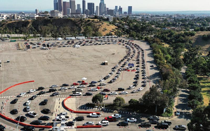 An aerial view of people in cars lined up to be tested for Covid-19 in a parking lot at Dodger Stadium in Los Angeles, California - Mario Tama/Getty Images North America