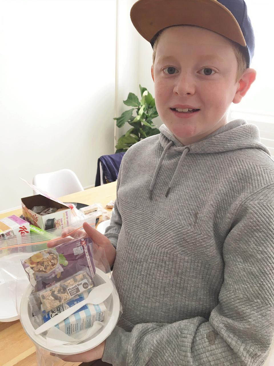 Photo shows Jackson holding a bag containing a muesli bar, cereal pack, milk, a napkin and a spoon.