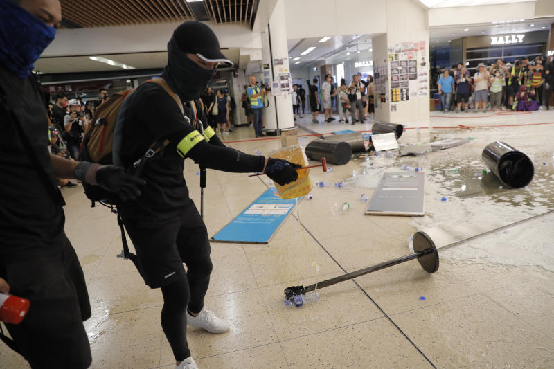 Protesters pour cooking oil onto the floor near a subway station in Hong Kong on Sunday, Sept. 22, 2019. Protesters smashed surveillance cameras and electronic ticket sensors in the subway station, as pro-democracy demonstrations took a violent turn once again. (AP Photo/Kin Cheung)