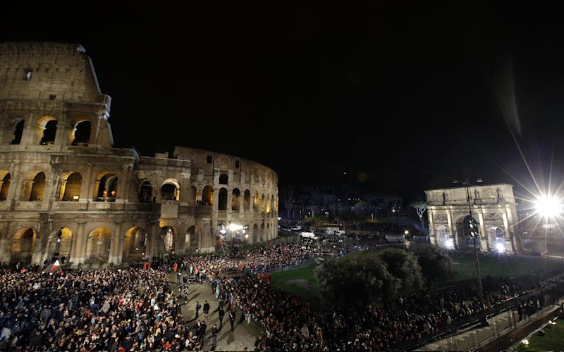 A crowd gathers beneath the ancient Colosseum prior to the start of the Via Crucis (Way of the Cross) torchlight procession which will be celebrated by Pope Francis, on Good Friday, in Rome, Friday, March 29, 2013. At right is the Arch of Constantine. (AP Photo/Andrew Medichini)