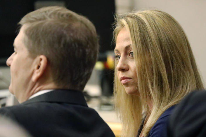 FILE - In this Sept. 25, 2019, file photo, fired Dallas police officer Amber Guyger looks toward her attorney before proceedings in her murder trial in Dallas. A Texas appeals court has upheld the murder conviction of Guyger, who was sentenced to prison for fatally shooting her neighbor in his home. A panel of three state judges on Thursday, Aug. 5, 2021, ruled that a Dallas County jury had sufficient evidence to convict Guyger of murder in the 2018 shooting of Botham Jean. (Tom Fox/The Dallas Morning News via AP, Pool, File)