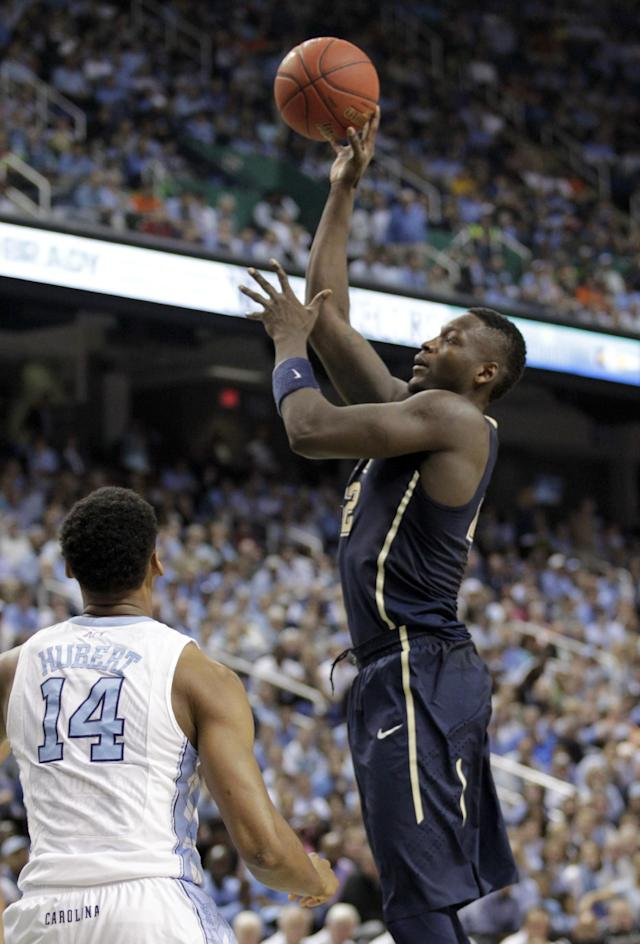 Pittsburgh's Talib Zanna (42) shoots over North Carolina's Desmond Hubert (14) during the second half of an NCAA college basketball game in the quarterfinal round of the Atlantic Coast Conference tournament in Greensboro, N.C., Friday, March 14, 2014. (AP Photo/Bob Leverone)