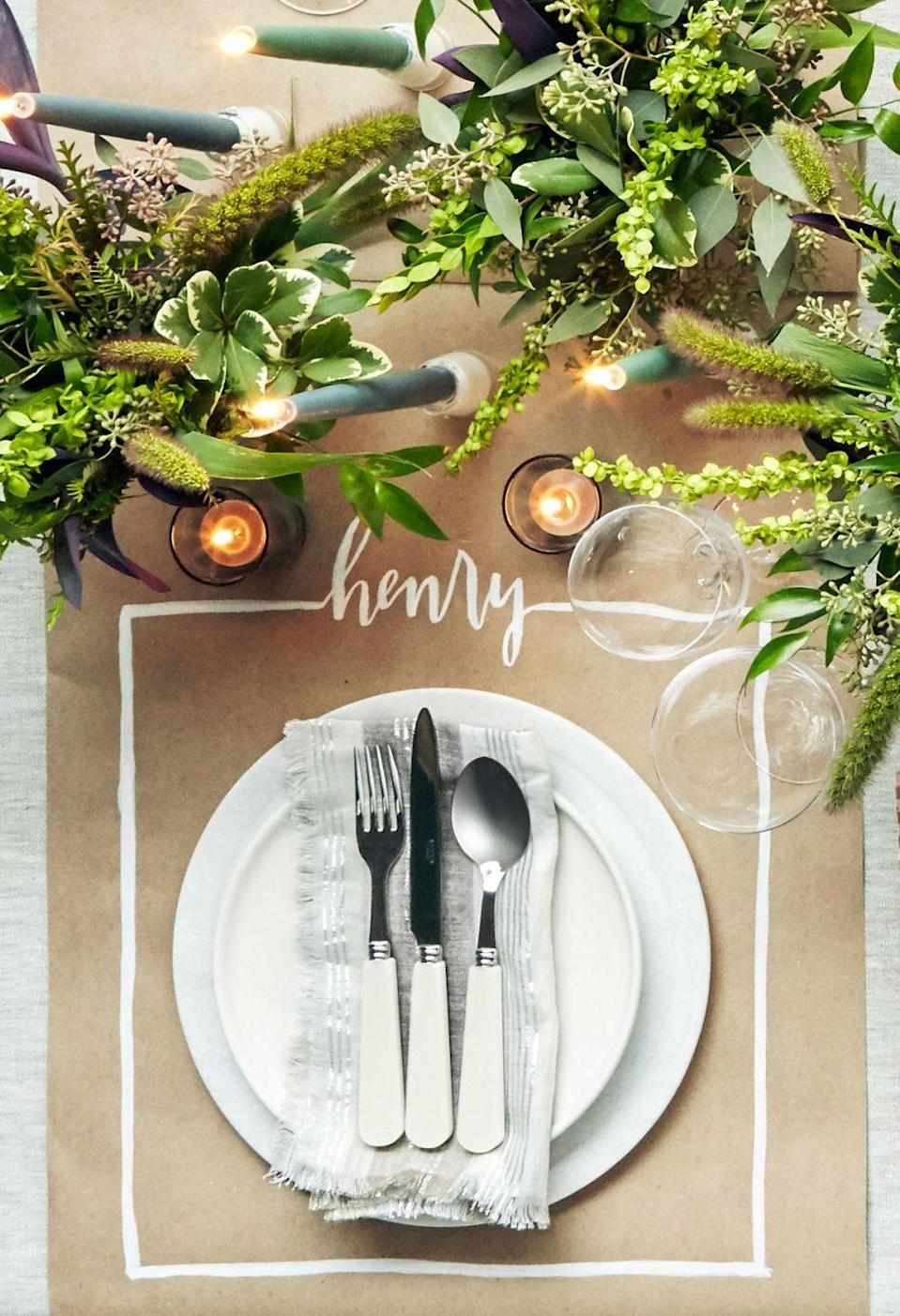 "<p>When it comes to place cards, there's no need to feel restricted by a tiny cardboard rectangle. Here, a table runner and a bit of <a href=""https://www.amazon.com/Testors-Enamel-Paint-Marker-Gloss-White/dp/B008CVNY34?tag=syn-yahoo-20&ascsubtag=%5Bartid%7C10050.g.1538%5Bsrc%7Cyahoo-us"" rel=""nofollow noopener"" target=""_blank"" data-ylk=""slk:white paint"" class=""link rapid-noclick-resp"">white paint</a> create a ""place mat"" that'll have everyone talking.</p><p><strong>Make the place mat: </strong>Cut an 18-inch-wide piece of kraft paper to desired runner length. In pencil, lightly draw three sides of a 16-inch square, leaving the top side open. Write the guest's name in the center of the open space, extending the lines on either side of the name to complete the square. Trace over the pencil lines with a white paint marker.</p><p><strong><a class=""link rapid-noclick-resp"" href=""https://www.amazon.com/Testors-Enamel-Paint-Marker-Gloss-White/dp/B008CVNY34?tag=syn-yahoo-20&ascsubtag=%5Bartid%7C10050.g.1538%5Bsrc%7Cyahoo-us"" rel=""nofollow noopener"" target=""_blank"" data-ylk=""slk:SHOP PAINT MARKER"">SHOP PAINT MARKER</a></strong></p>"