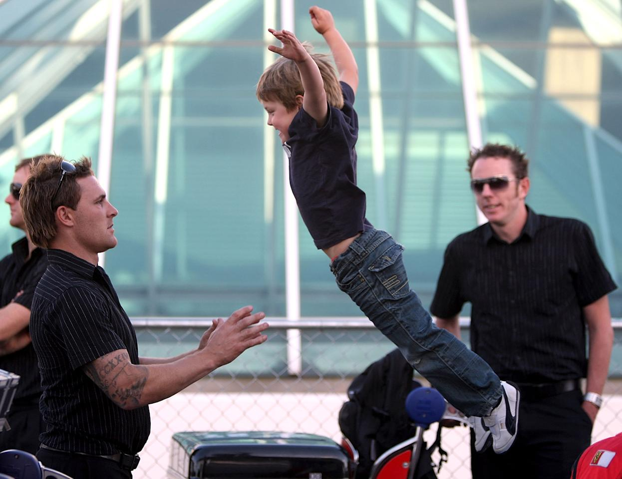 SYDNEY, AUSTRALIA - NOVEMBER 10:  Brendan McCullum of  New Zealand's son Riley jumps in to his father's arms as they wait for the bus at Sydney International Airport on November 10, 2008 in Sydney, Australia. The New Zealand team will play five Test matches,  five one day internationals and one Twenty20 international match during their tour of Australia.  (Photo by Ezra Shaw/Getty Images)