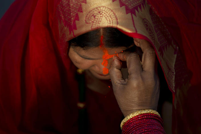 In this Saturday, Nov. 2, 2019, file photo, a Nepalese woman gets vermilion powder applied on her forehead after offering prayers to the setting sun at the Bagmati River during Chhath Puja festival in Kathmandu, Nepal. During Chhath, an ancient Hindu festival, rituals are performed to thank the sun god for sustaining life on earth. (AP Photo/Niranjan Shrestha, File)