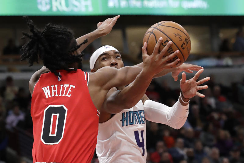 Charlotte Hornets guard Devonte' Graham, right, drives to the basket against Chicago Bulls guard Coby White during the first half of an NBA basketball game in Chicago, Thursday, Feb. 20, 2020. (AP Photo/Nam Y. Huh)
