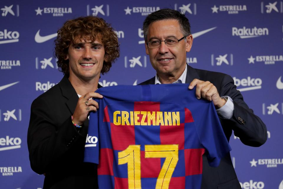 French forward Antoine Griezmann, left, holds up his new team shirt with FC Barcelona's President Josep Maria Bartomeu during his official presentation after signing for FC Barcelona in Barcelona, Spain, Sunday, July 14, 2019. (AP Photo/Emilio Morenatti)