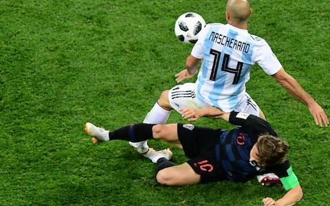 <span>Modric gets stuck in to Mascherano</span> <span>Credit: MARTIN BERNETTI/AFP/Getty Images </span>