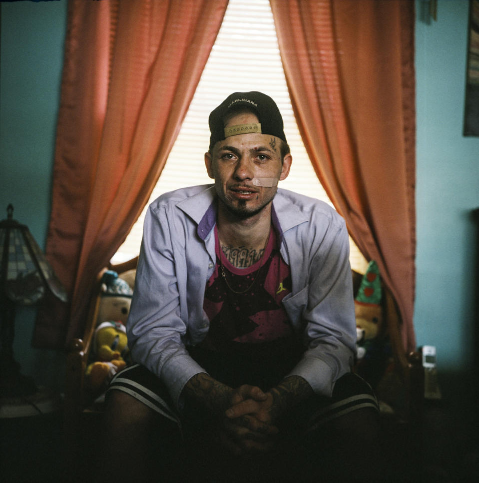 """In this photo made with a medium format film camera, Joshua Messer, 29, sits for a portrait in his aunt's home where he's currently staying, days after he overdosed, in Huntington, W.Va., Tuesday, March 16, 2021. Messer was a high school basketball star, heading to college on a scholarship. He still brags that he was such a star athlete he once met the governor of West Virginia. But addiction took hold, to alcohol and pills. """"I let my family down, now I'm trying to get it back together."""" He is covered in prison tattoos, and he likes bright colors and funny socks: he had Bugs Bunny on one foot and Mr. Potato Head on the other. He spent nine years in prison for an addiction-fueled burglary he barely remembers committing. In prison, he got 2020 tattooed on his chest because that was the year he was to be released and supposed to be the year he was to be reborn. He'd gotten a job as a cook at a restaurant and won employee of the month. He planned to save up money and open a landscaping business somewhere, get his own place and his own cat. Messer said the pandemic created a """"circle of nothing,"""" that drove him and other people he knows to using more drugs. He said he took heroin eight months ago for the first time and thought he could do it just once, but he woke up the next morning needing more. """"I look at some people and it's sad how they look,"""" he said. """"I'm starting to look like that. It's sad. I'm not better than other people. But I'm better than letting something take control of my life. I feel like I should be better than this."""" (AP Photo/David Goldman)"""