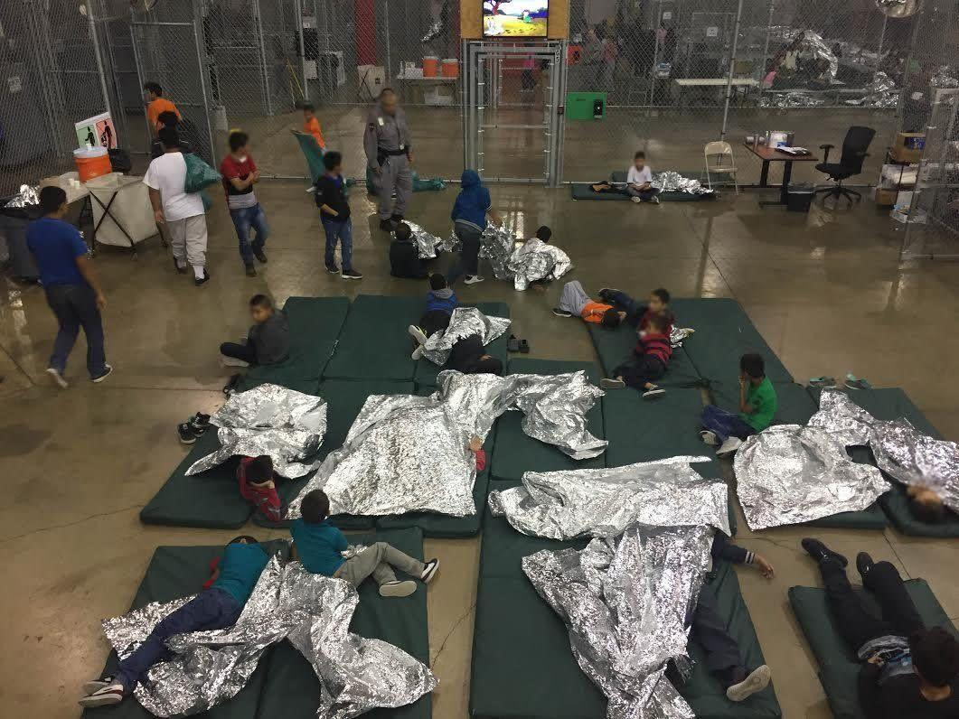 Migrant children sleep in what looks like a fenced-in area. The cage-like structures open up to common areas with portable restrooms, according to the AP.