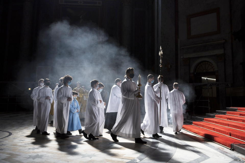 Clergyman and servers arrive for the Easter Sunday Mass celebrated by Primate of the Hungarian Catholic Church, Archbishop of Esztergom-Budapest, Cardinal Peter Erdo in the Esztergom Basilica in the City of Esztergom, Hungary, Sunday, April 4, 2021, during the pandemic coronavirus. The mass was broadcast on the Facebook account of the Archdiocese of Esztergom-Budapest and by a television channel as due to the pandemic of the novel coronavirus COVID-19 church services are not allowed to be attended by the public in Hungary. (Marton Monus/MTI via AP)