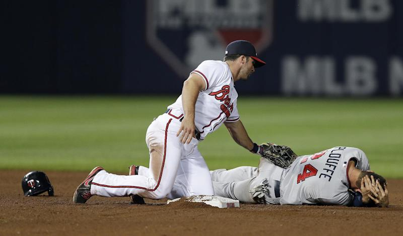 Atlanta Braves second baseman Dan Uggla (26) checks in Minnesota Twiins' Trevor Plouffe (24) after he was injured on a force out at second base on a ground ball in the ninth inning of a baseball game Tuesday, May 21, 2013 in in Atlanta. (AP Photo/John Bazemore)