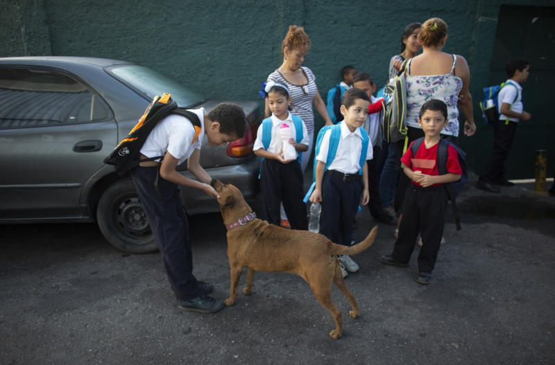 In this Oct. 2, 2019 photo, a boy pets his dog as he waits with other kids outside the Jerman Ubaldo Lira public school on their first day of class, in Caracas, Venezuela. The school year recently began amid the once-wealthy country's deepening crisis, with more teachers and students abandoning their homeland, leaving classrooms empty. Those remaining behind say they struggle to afford basic school supplies, some deciding not to attend at all, which experts say puts the next generation's chance for success in jeopardy. (AP Photo/Ariana Cubillos)