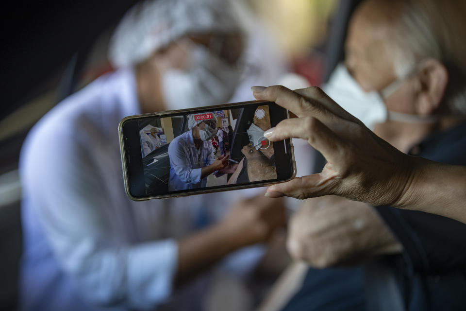 A woman films her father getting a shot of China's Sinovac CoronaVac vaccine during a priority COVID-19 vaccination program for the elderly at a drive-thru site set up in the Pacaembu soccer stadium parking lot in Sao Paulo, Brazil, Monday, Feb. 8, 2021. (AP Photo/Andre Penner)