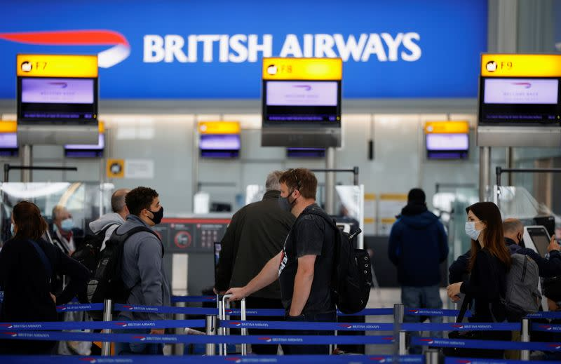 Passengers stand in a queue to the British Airways check-in desks at Heathrow Airport