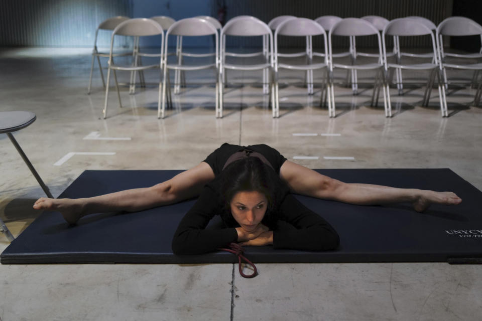 "Performer Alice Rende from Brazil stretches prior to performing ""Passages"", a contortionism creation in a space delimited by a Plexiglas box during the BIAC, International Circus Arts Biennale, in Marseille, south of France, Thursday, Feb. 4, 2021. (AP Photo/Francois Mori)"