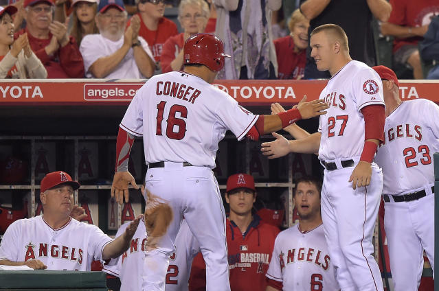 Los Angeles Angels' Hank Conger, center, is congratulated by manager Mike Scioscia, left, and teammate Mike Trout, second from right, after scoring on a ground out by Efren Navarro during the sixth inning of a baseball game against the Texas Rangers on Saturday, June 21, 2014, in Anaheim, Calif. (AP Photo/Mark J. Terrill)