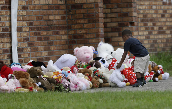 Fleming Clark, 2, places a teddy bear at a makeshift memorial near a trash bin where the body of missing 6-year-old Ahlittia North was said to have been found in Harvey, La., Tuesday, July 16, 2013. Her mother , Lisa North, says Jefferson Parish authorities have found the body of her daughter in a Harvey trash bin. Ahlittia disappeared from her apartment late Friday night or early Saturday morning. North's husband Albert Hill said they were told the body was found in a trash bin not far from their apartment. (AP Photo/Gerald Herbert)
