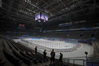 Volunteers and officials view the ice hockey venue for the 2022 Beijing Winter Olympics at the National Indoor Stadium in Beijing, Thursday, April 1, 2021. Chinese capital holds 10 days test events for 2022 Beijing Winter Olympics in five different venues from April 1-10 and becomes the first city to hold both the Winter and Summer Olympics. (AP Photo/Andy Wong)