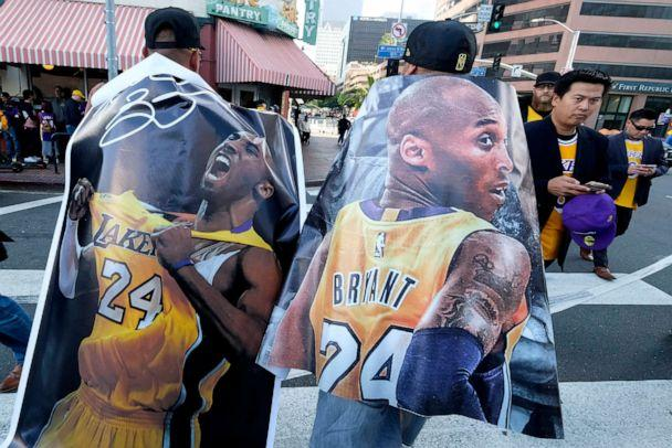 PHOTO: Fans carry posters of Kobe Bryant near the Staples Center before a public memorial for former Los Angeles Lakers star Kobe Bryant and his daughter, Gianna, in Los Angeles, Feb. 24, 2020. (Ringo H.W. Chiu/AP)