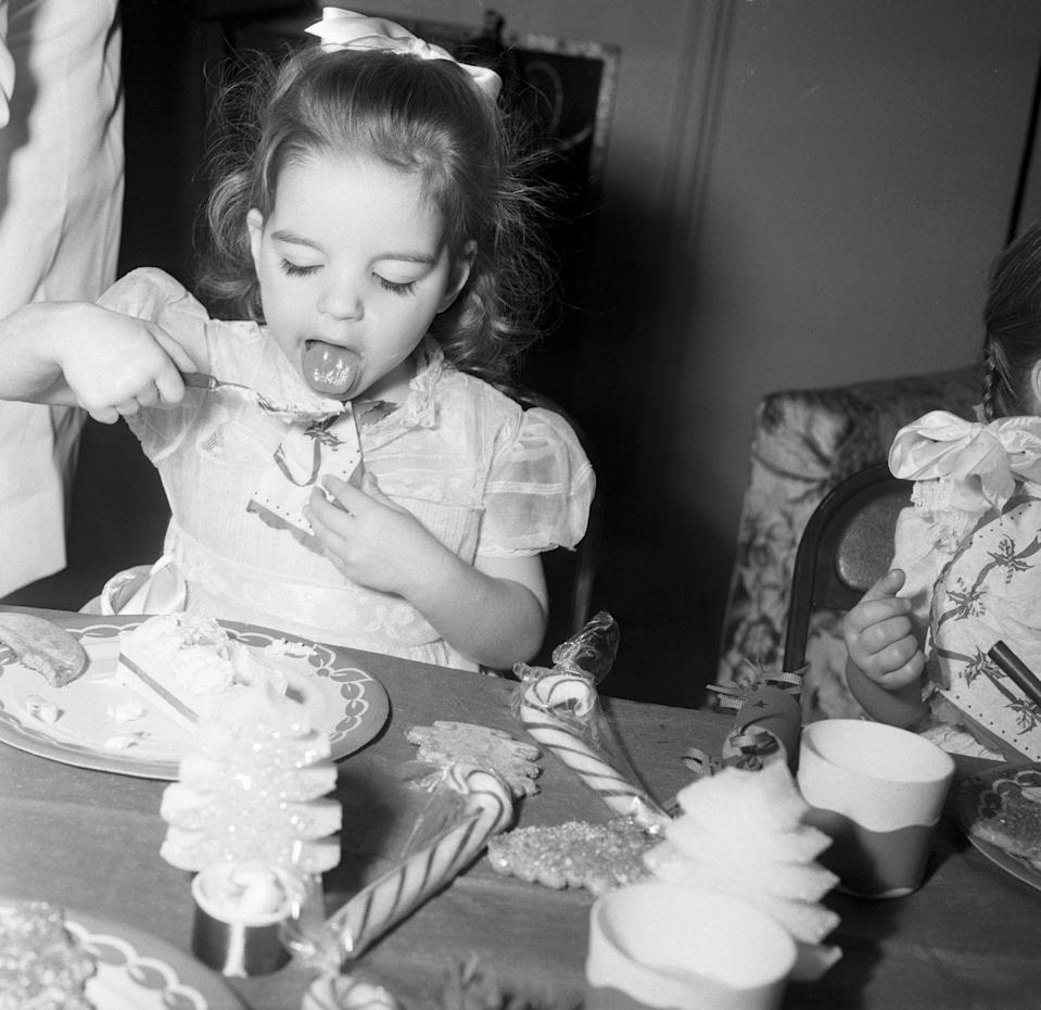 <p>Judy Garland's young daughter, Liza Minnelli, makes the most of a holiday party by chowing down on ice cream and candy, as one does.</p>