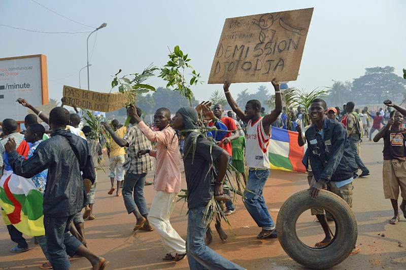 """Anti Seleka demonstrators holding a placard reading """"Djotodia Resign"""" march to Mpoko airport on January 10, 2014 in Bangui (AFP Photo/Eric Feferberg)"""