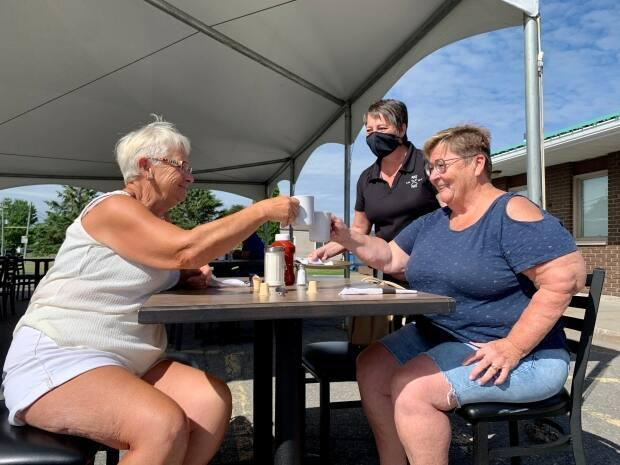 Patrons toast at Place 1967 in Plantagenet, east of Ottawa, as server Sylvie Groulx looks on Friday morning. Outdoor dining at eastern Ontario restaurants is allowed again for the first time since early April. (Denis Babin/Radio-Canada - image credit)