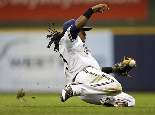Milwaukee Brewers second baseman Rickie Weeks makes a falling try at a ball hit by San Diego Padres' Will Venable, who singled during the seventh inning of a baseball game Tuesday, July 23, 2013, in Milwaukee. (AP Photo/Morry Gash)