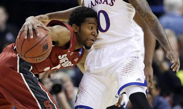 Stanford's Chasson Randle, left, tries to maneuver around Kansas' Naadir Tharpe, right, during the first half of a third-round game of the NCAA college basketball tournament Sunday, March 23, 2014, in St. Louis. (AP Photo/Jeff Roberson)
