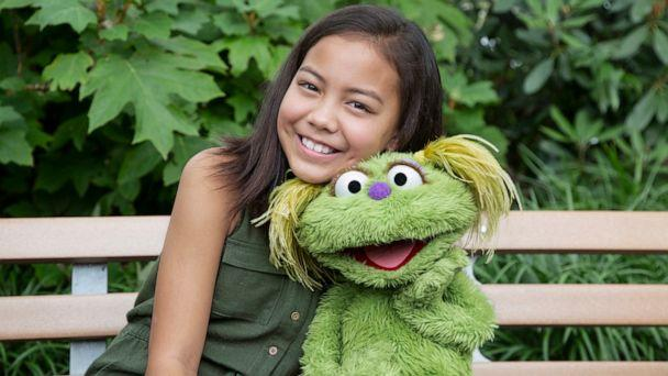 PHOTO: Salia Woodbury, whose parents are in recovery sits with 'Sesame Street' character Karli. (Flynn Larsen/Sesame Workshop via AP)